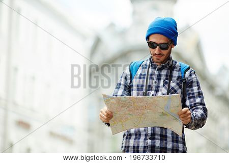 Portrait of contemporary young man on solo trip in Europe, standing in street of old city looking at map tourist guide