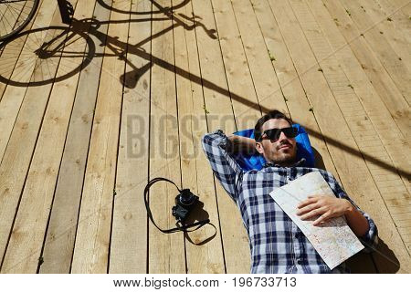 Above view of handsome young man lying on wooden dock planks in sunlight holding map, camera and bicycle nearby