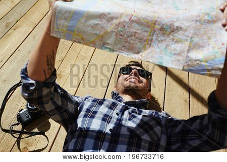 Above view of handsome young man lying on wooden dock planks in sunlight looking at map for directions enjoying tourist trip