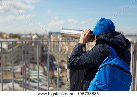 Back view portrait of contemporary tourist looking over city from viewing platform on the roof, using coin operated binoculars