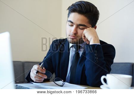 Napping manager sitting by workplace