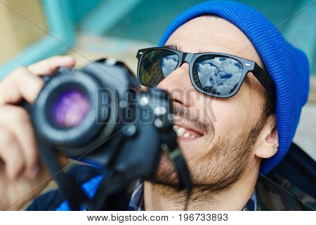 Portrait of happy handsome man taking photos and looking up enjoying tourist trip