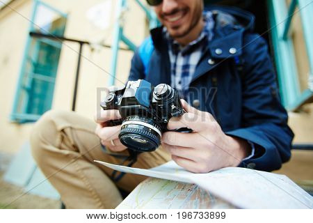 Closeup image of photo camera in hands of young tourist browsing pictures while traveling on solo trip in streets of old city