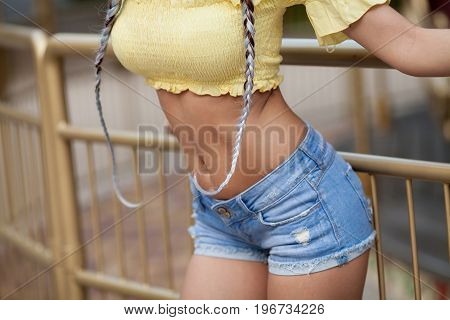 Sexy flat belly of a woman in blue jeans shorts outdoor.