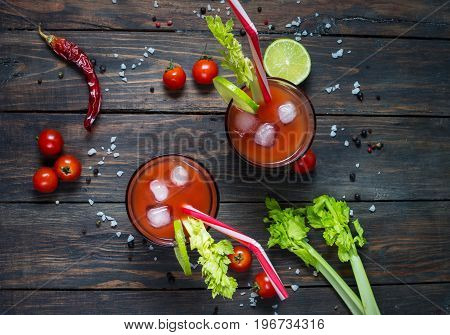 Cocktail Bloody Mary with ice in glasses on a wooden table. Top view