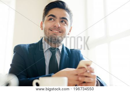 Young agent in suit holding smartphone in hands