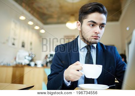 Young man in suit sitting in cafe and job hunting