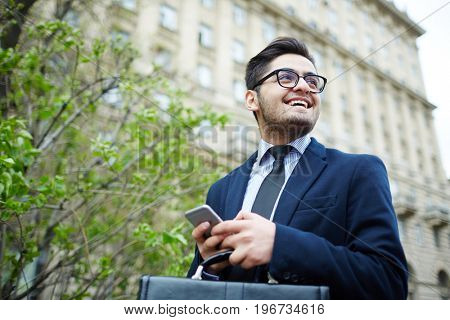 Smiling professional with smartphone walking in the city