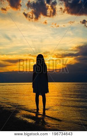 Girl standing in the sea on a background picturesque sunset on a summer evening