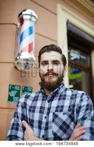 Young barber standing by barbershop