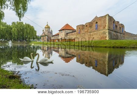 Fagaras Fortress - June 4: Fagaras fortress in the middle of the lake near the cathedral under renovation in Fagaras Brasov county Romania.