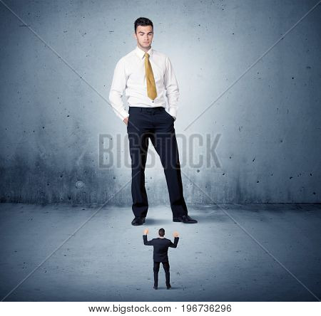 Angry huge business man lokking at small coworker guy concept on background
