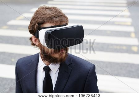 Modern man wearing headset while crossing road
