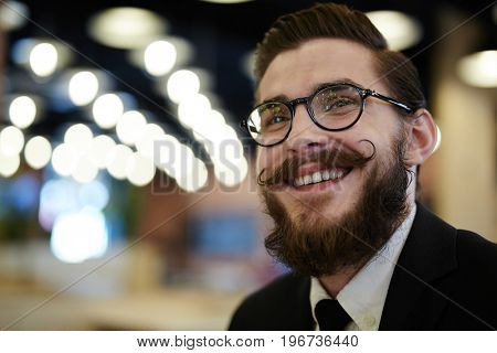 Happy businessman in eyeglasses on night city background