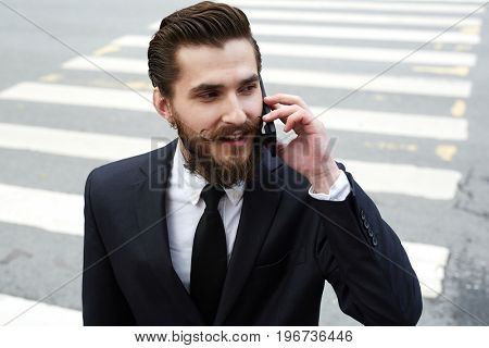 Handsome businessman in suit speaking on smartphone while crossing road