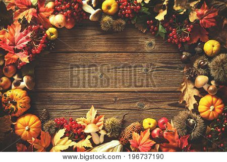 Vintage autumn border from fallen leaves and fruits on the old wooden table. Thanksgiving autumnal background