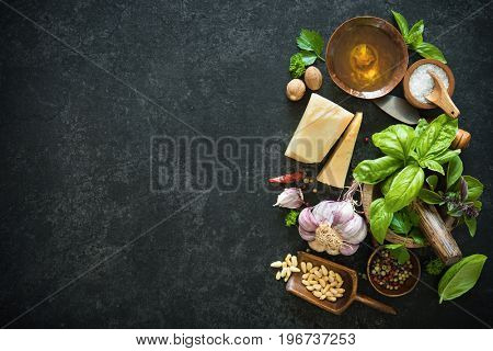 Ingredients for homemade green basil pesto on black stone table. Parmesan cheese, basil leaves, pine nuts, olive oil, garlic, salt and pepper