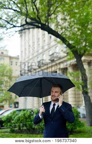 Young businessman in suit talking on mobile phone under umbrella