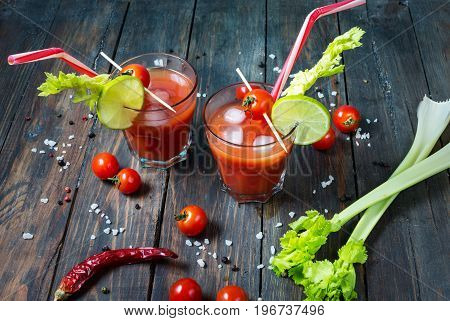 Cocktail Bloody Mary with ice in glasses on a wooden table.