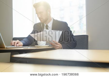 Mobile businessman concentrating on network in cafe