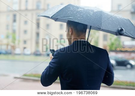 Rear view of busy ceo messaging in rainy weather