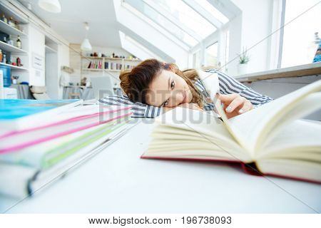Cute learner lying on desk with open book in front of her face