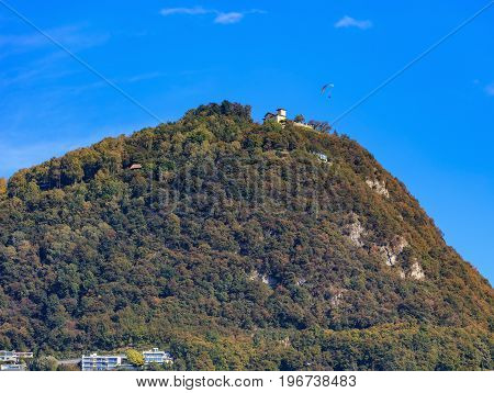 Summit of the Monte Bre mountain in Switzerland as seen from the city of Lugano in the Swiss canton of Ticino, a paraglider flying over it. The picture was taken at the middle of autumn.