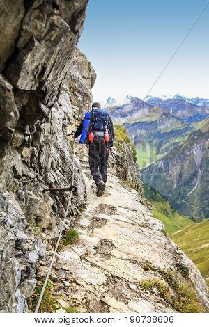 Man walks on dangerous fixed rope route in alpine mountains. Very exposed, great view. Hiking and climbing in the mountains.