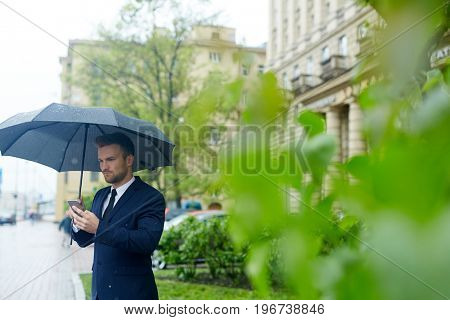 Businessman waiting for co-worker on rainy day outdoors