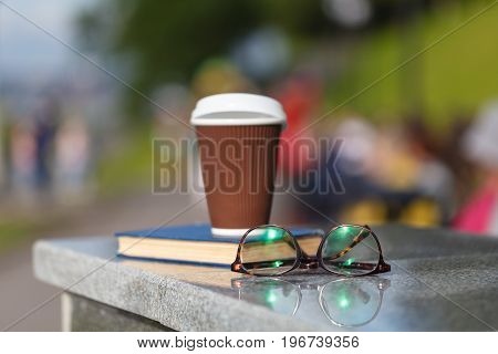 Coffee cup with book on stone table in city