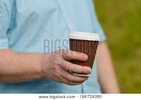 Man's Hand Holding Paper Cup Of Coffee. Drink On Street
