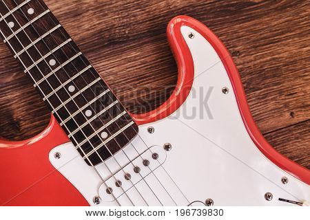 Part of modern electric six string guitar red color with glossy finish pickups and control knobs isolated on wooden background close up view.