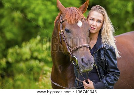Smiling and beautiful young woman with her adult arabian horse standing in a field. Relationship between human and animal.