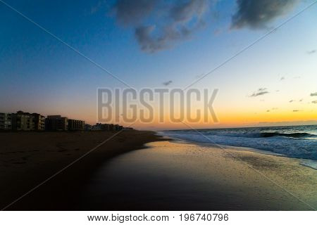 Divided Beach Sunset With Yellow and Orange Colors and Blue Sky and Dark-Gray Clouds