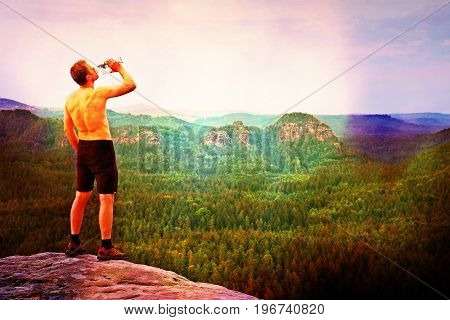 Film Effect. Thirsty Hiker In Black Pants With Bottle Of Water. Sweaty Tired Tourist