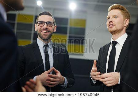 Elegant professionals talking to business partner