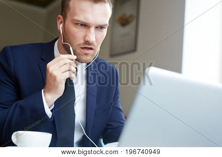Businessman with earphones making video call
