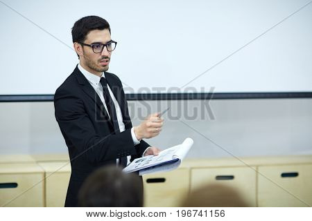 Confident trader making financial report at conference