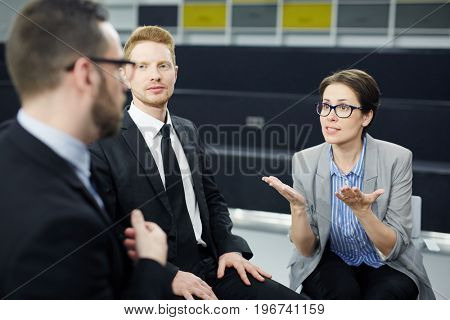 Confident woman voicing her opinion to colleagues