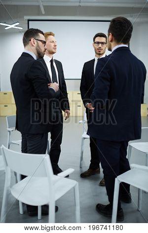 Four businessmen in suits talking in auditorium