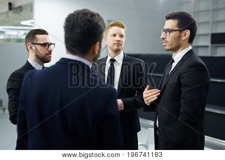 Team of businessmen listening to their leader at meeting