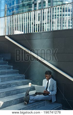 Young manager networking while sitting on staircase in urban environment