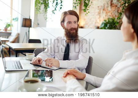 Small business team sitting in cafe and discussing project