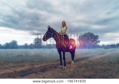happy attractive girl sitting on horse back and laughs