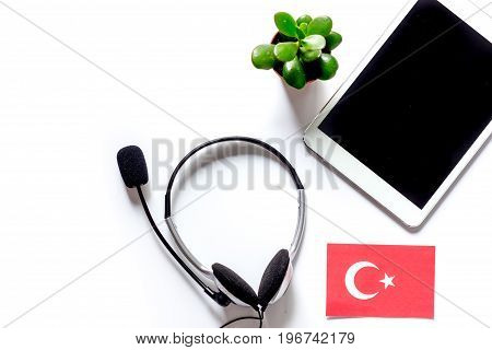 Self-education. Learning languages online. Headphones and tablet PC on white table background top view.