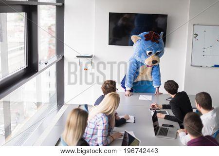 Boss dresed as teddy bear having fun with bussines people in modern corporate office