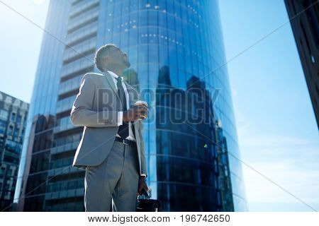 Businessman with drink looking at modern skyscraper