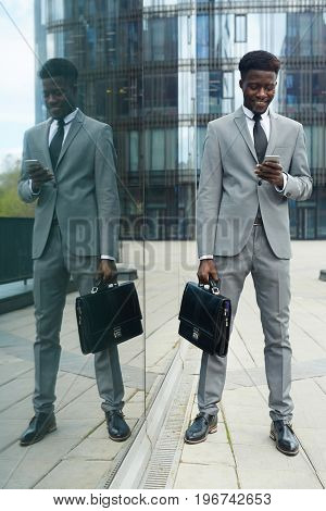Busy entrepreneur with smartphone and briefcase messaging outdoors