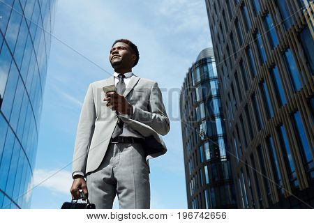 Urban businessman with briefcase and smartphone