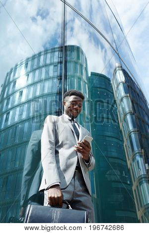 Happy businessman texting against modern building